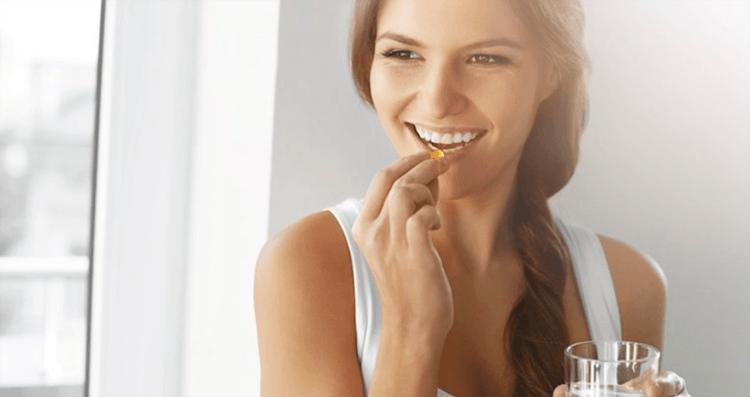 Девушка кладет в рот капсулу с витаминами
