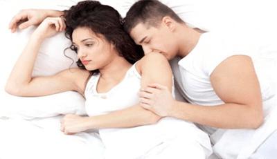 Девушка отвернувшись от парня лежит на кровати