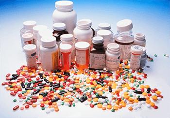 Таблетки и капсулы рассыпаны возле банок из под препаратов