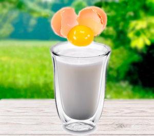 Стакан молока на столе с разбитым яйцом картинка