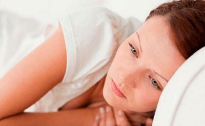 Женщина задумчиво смотрит лежа на кровати