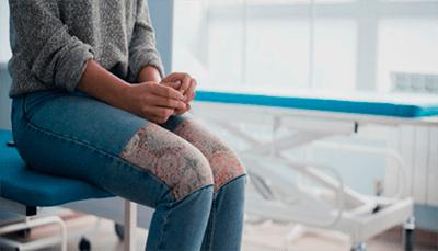 Женщина сидит на краю кушетки в больнице
