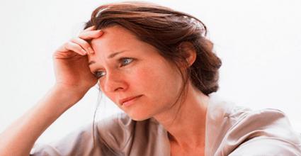 Опечаленная женщина сидит взявшись рукой за голову