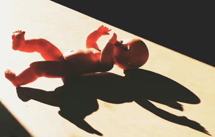Пластиковая кукла лежит на полу в полумраке