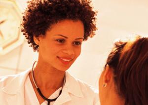 Женщина врач смотрит с улыбкой на пациентку